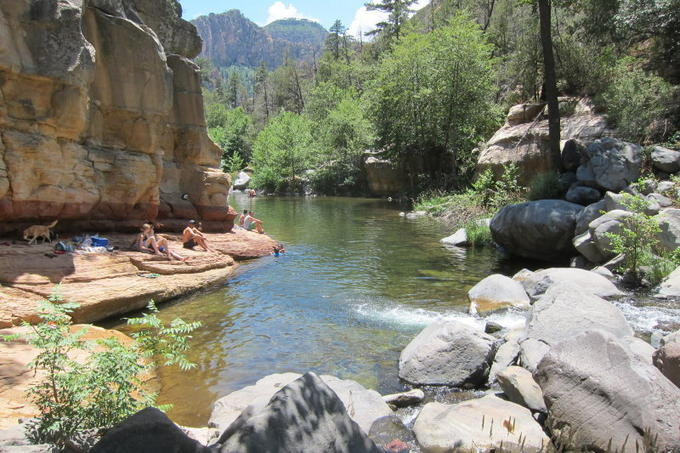 People sunning thensleves in Oak Creek Canyon beside the creek