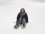 A woman sittin gon the ice at Arcadia Ice Arena
